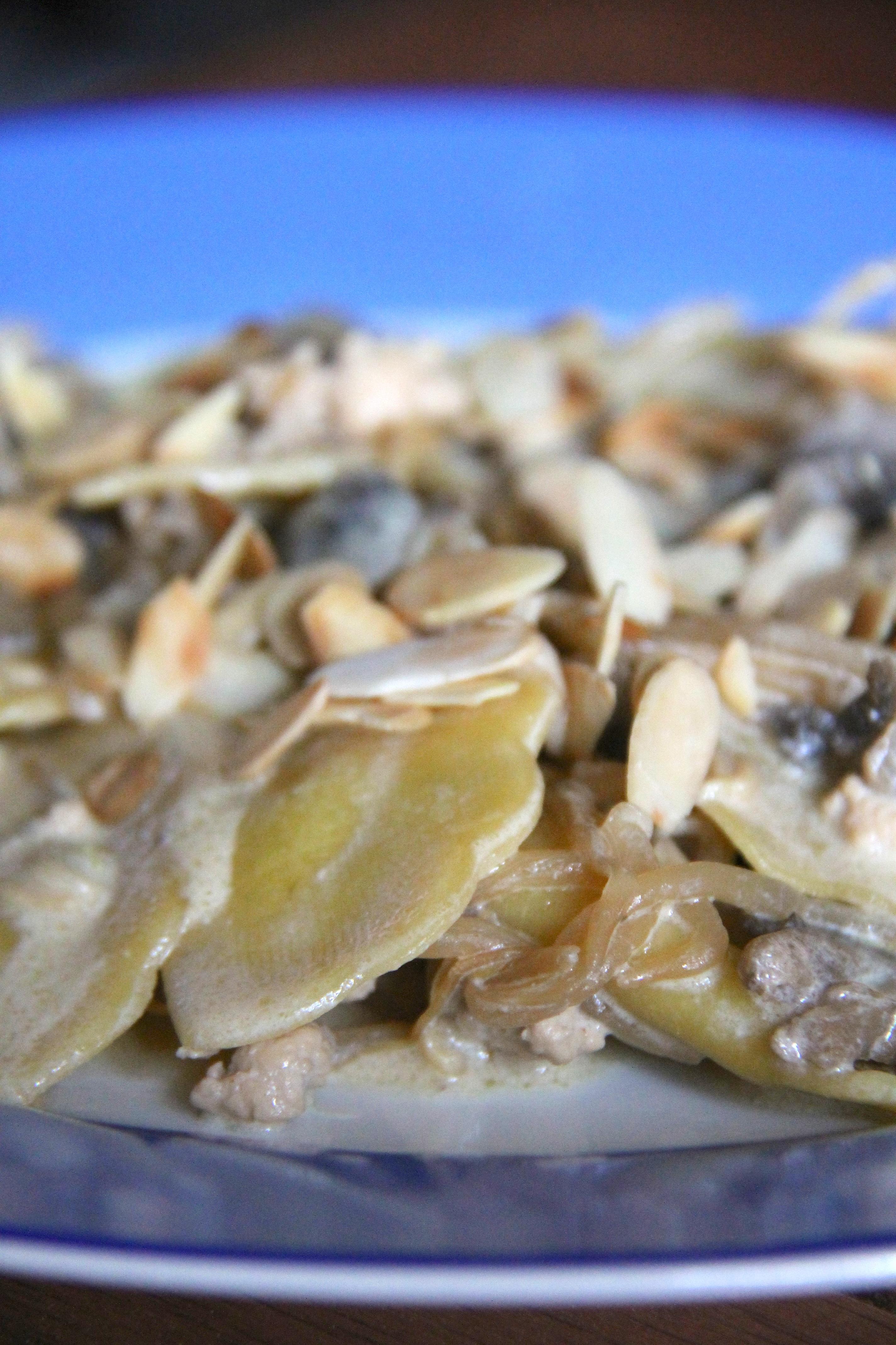 Ravioli mezzelune al pistacchio con ragù di pollo, funghi e scaglie di mandorle