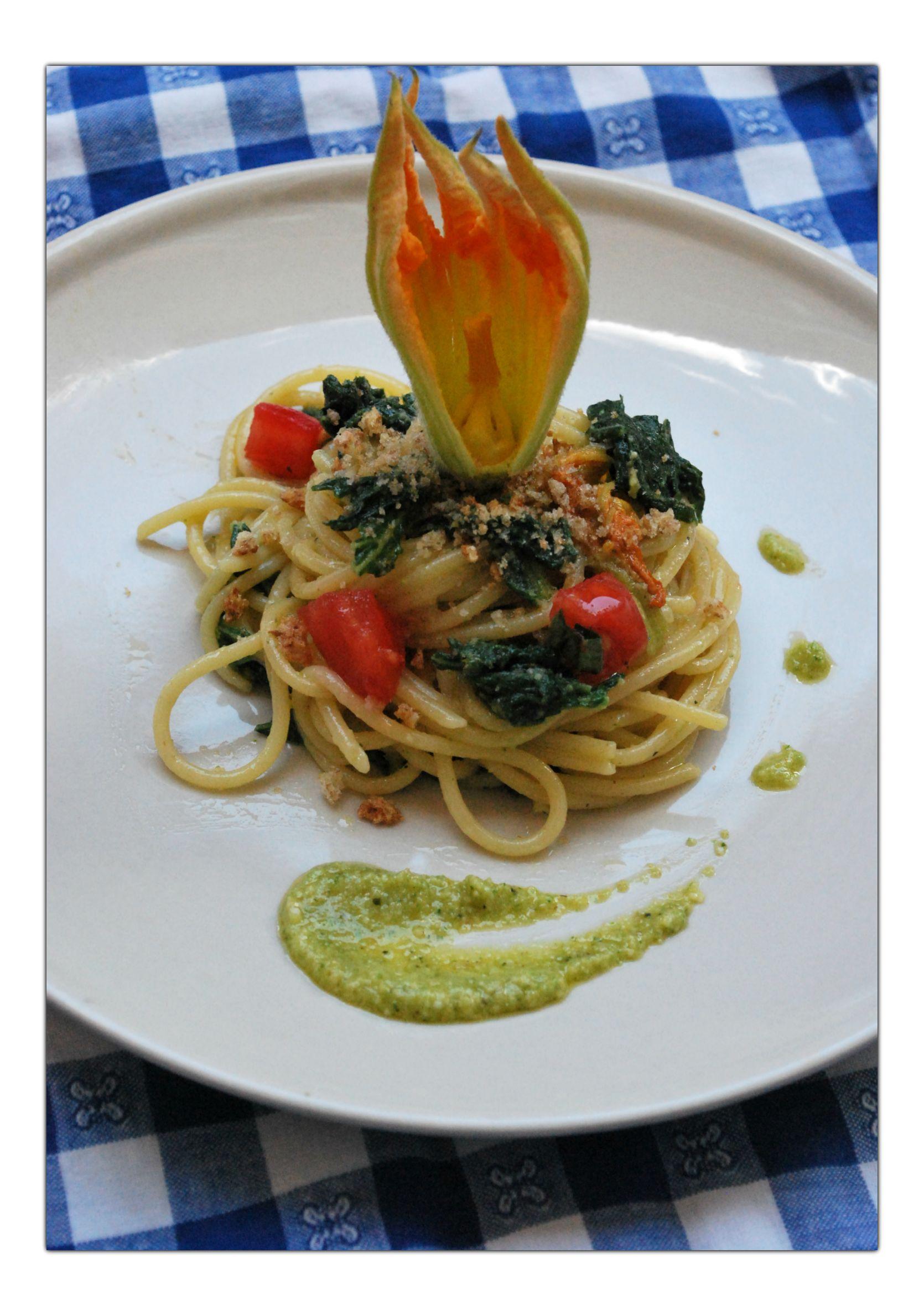 Spaghetti con fiori, foglie e pesto di zucchine, dadini di pomodori e pangrattato piccante